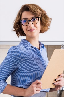 Portrait of young woman holding clipboard in hands