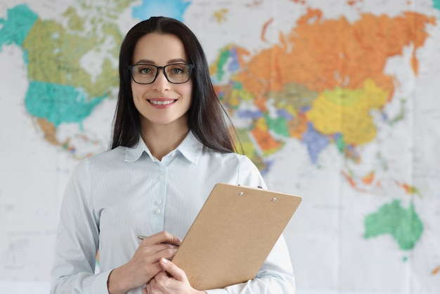 Portrait of young woman holding clipboard with documents in background map of world