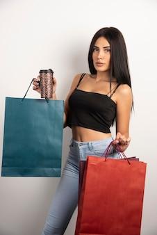 Ritratto di giovane donna che tiene caffè e borse della spesa. foto di alta qualità