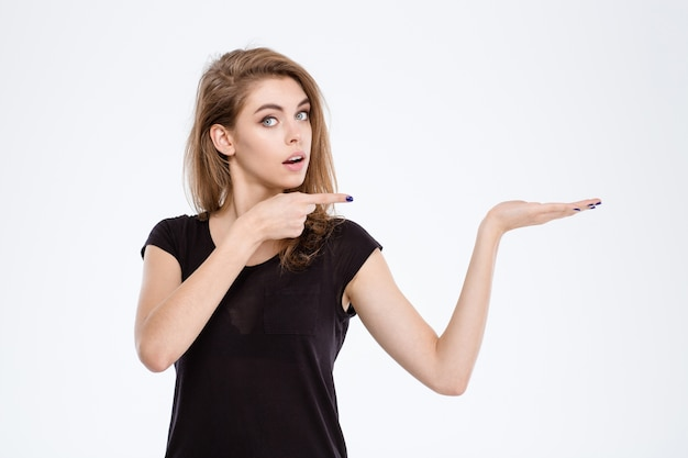 Portrait of a young woman holding copyspace on the palm and pointing finger on it isolated on a white background
