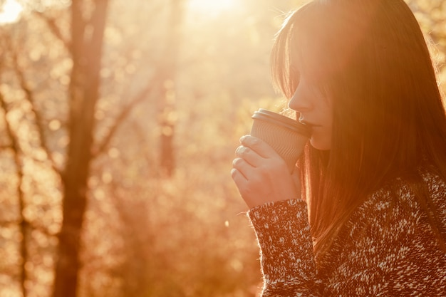 Portrait of young woman holding cup of coffee in the autumn park. warm sunny weather. outdoors