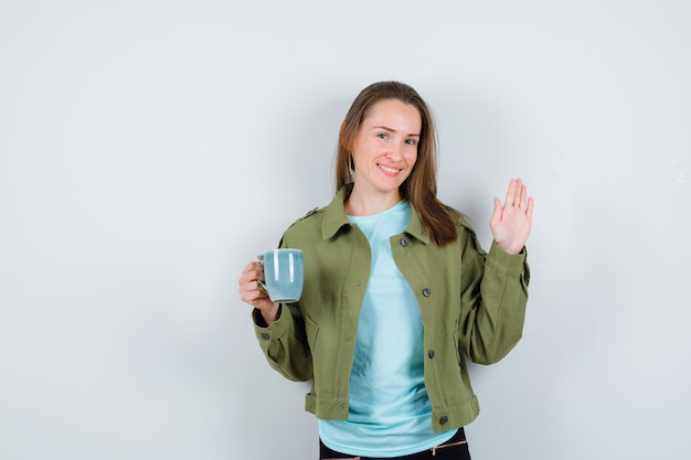 Ritratto di giovane donna che tiene una tazza di bevanda, saluta con la mano aperta in maglietta, giacca e sembra allegra vista frontale
