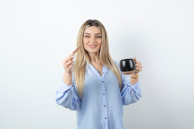 Portrait of young woman holding cup of hot drink with chocolate bar