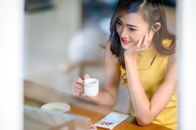 Portrait of young woman holding cup of tea while sitting at cafe