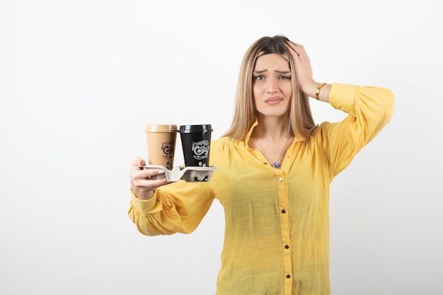 Portrait of young woman holding cups of coffee and standing on white.