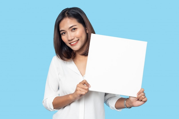 Portrait of young woman holding empty white canvas frame for text or ad isolated on blue background