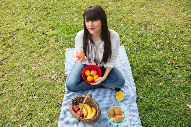 Portrait of young woman holding fresh fruits in the park