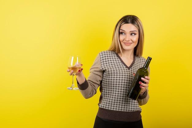 Ritratto di giovane donna con bicchiere e bottiglia di vino bianco.
