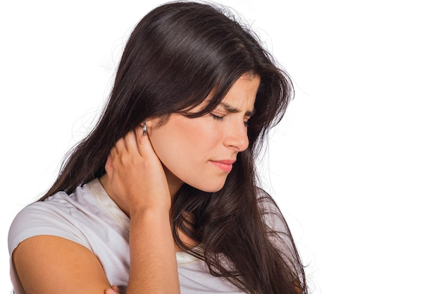 Portrait of young woman holding hand on neck with neck pain in studio. health concept.