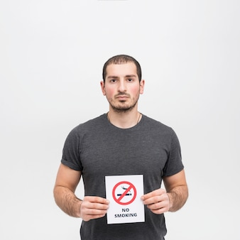 Portrait of a young woman holding no smoking sign against white background