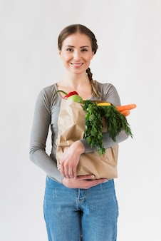 Portrait of young woman holding paper bag with groceries