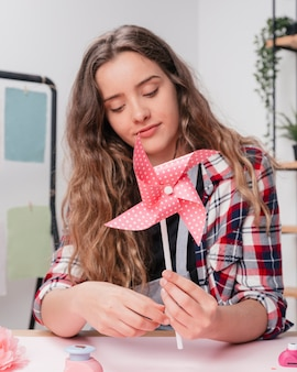 Portrait of a young woman holding pink origami polka dotted pinwheel