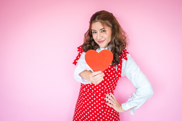 Portrait of young woman holding red heart in front of her