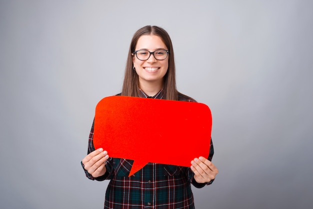 Portrait of young woman holding red speech bubble with copyspace