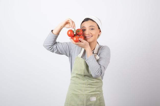 Ritratto di giovane donna con pomodori rossi su muro bianco