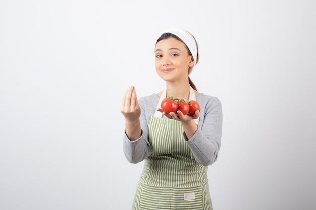 Ritratto di giovane donna con pomodori rossi su muro bianco Foto Gratuite