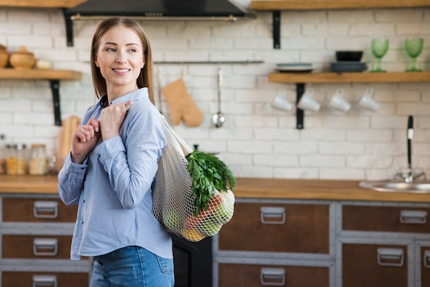 Portrait of young woman holding reusable bag with groceries