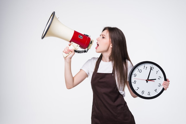 Portrait of young woman holding round clock, scream in megaphone isolated.