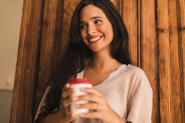 Portrait of young woman holding takeaway coffee cup