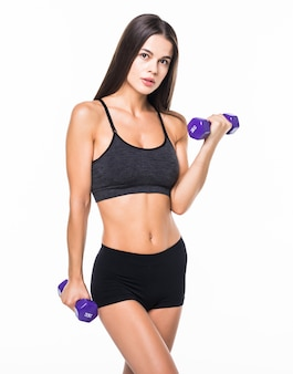 Portrait of a young woman holding weights and doing fitness against a white