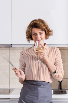 Portrait of a young woman holding whisk in hand drinking the wine