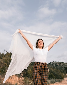 Portrait of a young woman holding white scarf raising her hands enjoying the nature