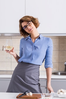 Portrait of a young woman holding wineglass in hand daydreaming