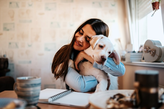 Portrait of a young woman hugging puppy indoors.