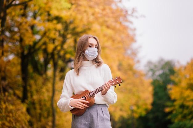 가을 공원, 라이프 스타일 건강 여행 개념에서 우쿨렐레 기타를 연주 보호 마스크에 세로 젊은 여자