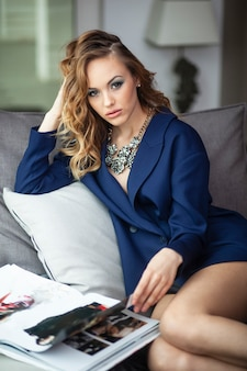 Portrait of a young woman is lying on a couch, wear blue suit with decolletage and accessory, browses a magazine.