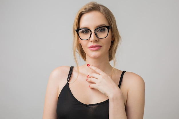 Portrait of young woman isolated on white wearing glasses in confident pose and wearing black dress
