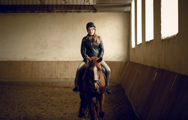 Portrait of young woman jockey sitting on brown horse at indoor arena