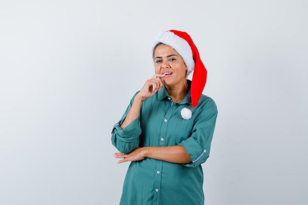 Ritratto di giovane donna che tiene il dito sul labbro inferiore in camicia, cappello da babbo natale e guarda una vista frontale pensierosa