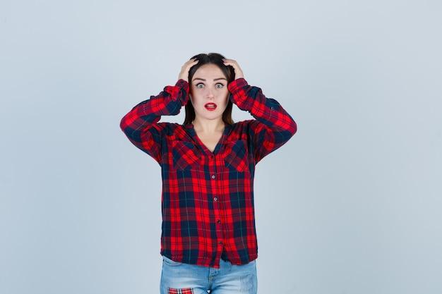 Ritratto di giovane donna che tiene le mani sulla testa in camicia a quadri, jeans e sembra scioccata vista frontale
