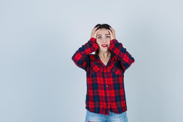 Ritratto di giovane donna che tiene le mani sulla testa in camicia a quadri e sembra eccitata vista frontale