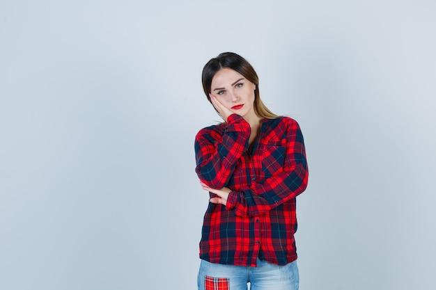 Ritratto di giovane donna appoggiata guancia sul palmo in camicia a quadri e guardando triste vista frontale