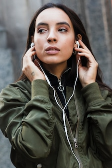 Portrait of a young woman listening music on white earphone