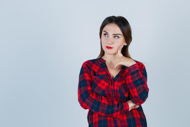 Ritratto di giovane donna che distoglie lo sguardo con il dito sulla guancia in camicia a quadri e guardando la vista frontale pensierosa