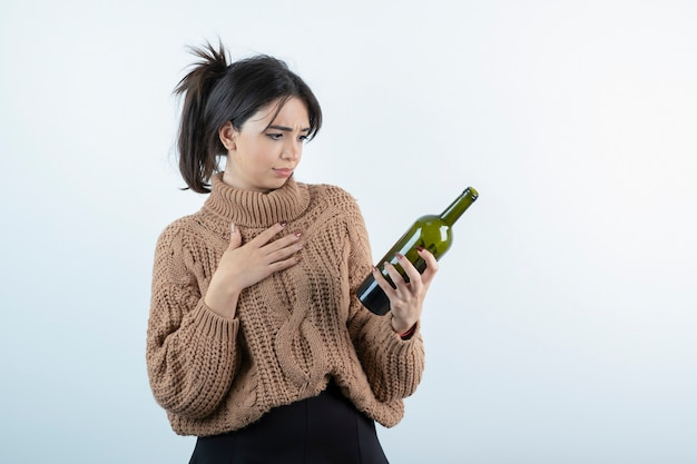 Portrait of young woman looking at bottle of wine on white wall