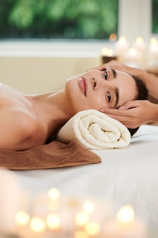 Portrait of young woman looking at camera while lying and getting spa procedure