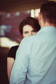 Portrait of young woman looking from behind the shoulder of her boyfriend