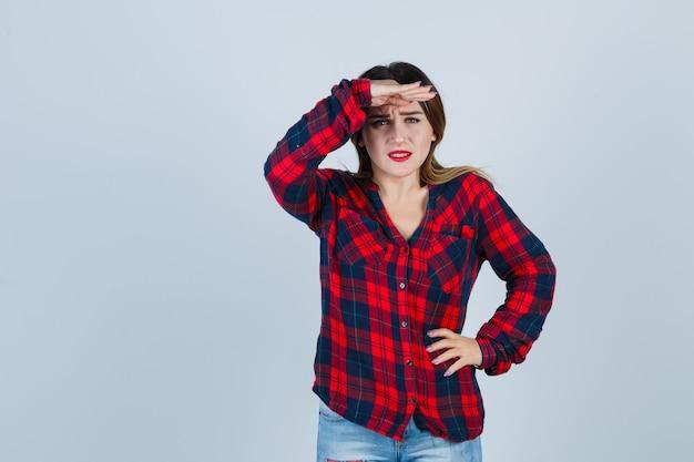 Ritratto di giovane donna che guarda davanti con la mano sopra la testa in camicia a quadri e sembra confusa vista frontale