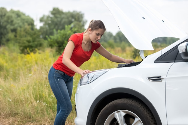 Portrait of young woman looking under the hood of broken car at rural road
