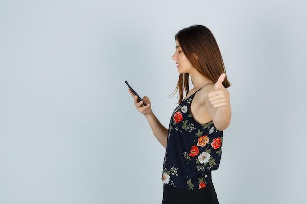 Ritratto di giovane donna che guarda lo smartphone, mostra il pollice in camicetta, gonna e sembra occupata