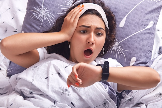 Portrait of young woman lying in bed on pillow and under blanket with dandelion, being at home in her cosy room, keeps mouth opened, looking at watch with astonish facial expression, being late.