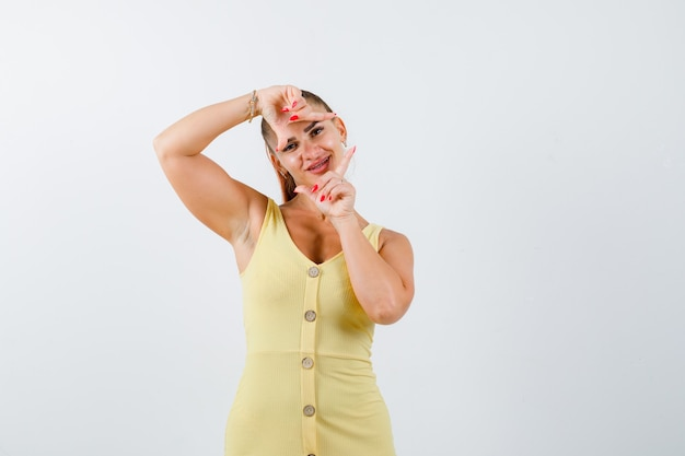 Portrait of young woman making frame gesture in yellow dress and looking cheery front view