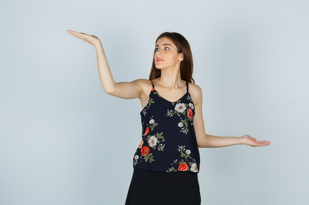 Portrait of young woman making scales gesture in blouse, skirt and looking confident front view