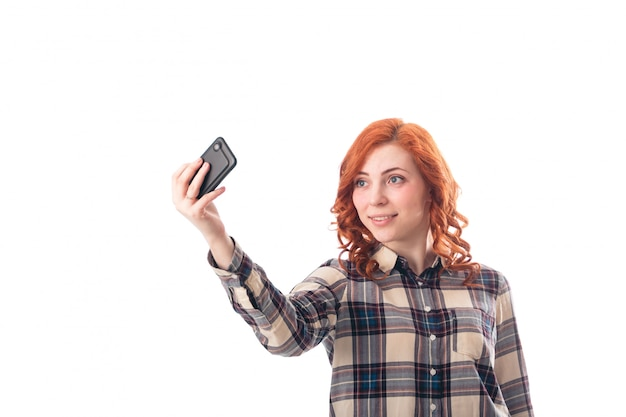 Portrait of a young woman making selfie photo on smartphone