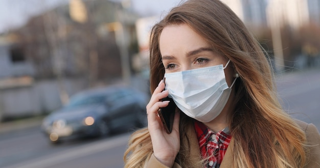 Portrait of young woman in medical face mask calling on cell phone while standing on street in the city. pandemic concept.