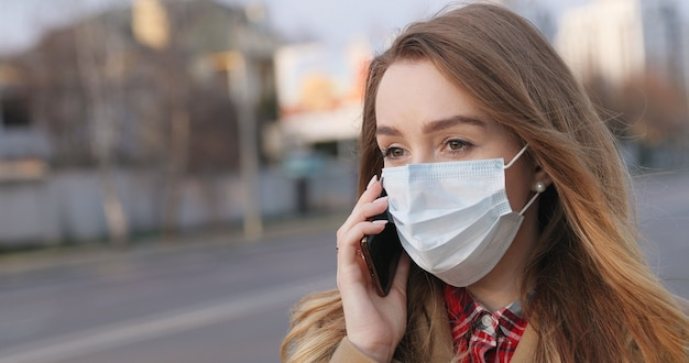 Portrait of young woman in medical face mask talking on a smartphone on the street. coronavirus quarantine. pandemic concept, coronavirus epidemic.